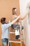 Home improvement: Young couple painting wall Royalty Free Stock Photos