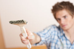 Home improvement: Young man holding paint brush Stock Images