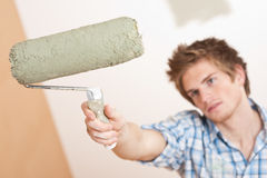 Home improvement: Young man holding paint roller Stock Photography