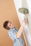 Home improvement: Young man with paint roller Stock Images