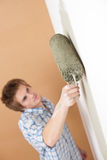 Home improvement: Young man with paint roller Royalty Free Stock Photos
