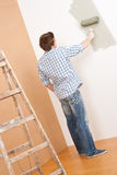 Home improvement: Young man with paint roller Stock Photo