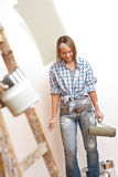 Home improvement: Young woman with paint roller. And ladder painting wall Royalty Free Stock Photo