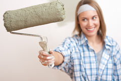 Home improvement: Young woman with paint roller Stock Images