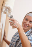 Home improvement: Young woman painting wall Stock Photo