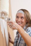 Home improvement: Young woman painting wall Royalty Free Stock Image