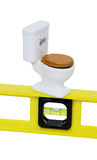 Home improvements. Porcelain toilet with wooden seat with yellow level with bubbles and measuring indicators Stock Images