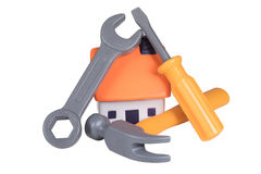 Home improvements and renovation concept. Home improvements, DIY and renovation concept with a still life of assorted tools on a small model house isolated on stock photos
