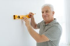 Home improvements. Senior man checking walls of his flat with level Stock Photos