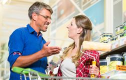 Home improver couple buying paint and painter tools in hardware Royalty Free Stock Images