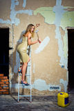 Home improvments. Girl on a ladder with a hummer in her hand Stock Photos