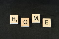 Home. Inscription home with bricks on a black background Stock Photography