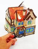 Home Inspection. A ceramic cookie jar house and a hand holding a magnifying glass in front of it. A concept of home inspection royalty free stock images