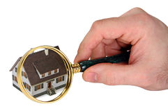 Home inspection concept. Concept image of a home inspection. A male hand holds a magnifying glass over a miniature house. White background Royalty Free Stock Image