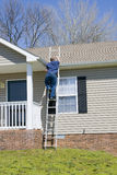 Home inspector. Inspector climbing ladder, checking damaged roof on home after recent wind storms, many roofs were damaged Stock Photo