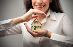 Home insurance. Closeup on woman's hands proecting a house Stock Photography