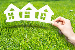 Home insurance concept with hand holding house shaped printouts on green grass stock image
