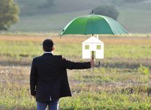 Home insurance protection concept, businessman with umbrella Stock Photos