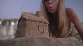 Home Insurance and Protection. Small house with a roof made of sand on the beach at sunset. Property insurance, house protection or saving and security concept stock video footage