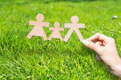 Home insurance to protect your family concept. With woman holding human shaped cardboard silhouettes Stock Image