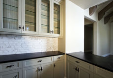 Home interior bar area. Bar area of kitchen in new home interior with glass faced white wood cabinetry Stock Photos