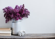 Home interior decor. Bouquet of lilacs in a vase and books on rustic wooden table, on a white wall background Royalty Free Stock Photo