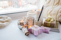 Home interior decor in brown colors: glass jar with aroma stick, candles and romance gift box on white windowsill. Living room. Decoration, cozy home, romantic royalty free stock images