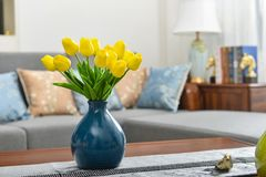 Home interior decor, tulip bouquet in vase. Home interior decor,tulip bouquet in a vase on wooden table runner, in living room Royalty Free Stock Images