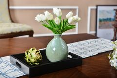 Home interior decor, white tulip bouquet in vase. Home interior decor,tulip bouquet   in a vase  on wooden table  runner, in living room Stock Photo