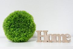 Home Interior Decoration - Green Grass Ball With Wooden Home Letters On White Background stock images