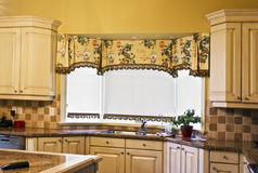 Home Interior: Kitchen. Kitchen counter with granite top and valence on window royalty free stock images