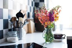 Home interior of modern kitchen. Bunch of fresh summer flowers in a jug in home interior of modern kitchen, close-up Stock Images