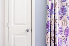 Home interior showing  colonial closet door with purple curtain decor and light blue painted wall stock image
