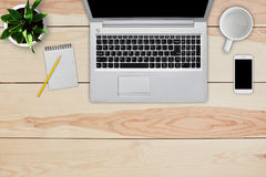Free Home Interior. Top View Of Wooden Desk With Laptop, Cell Phone, Blank Notebook For Text And Pencil, Empty White Mug And Green Flow Royalty Free Stock Images - 95406129