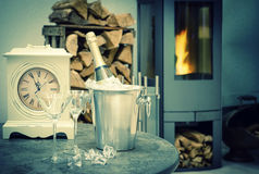 Home interior wirh champagne, fireplace and vintage clock Stock Photography