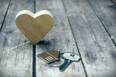 Home key with house keychain and wooden heart mock up on vintage wood background, home sweet home concept. Copy space stock photos