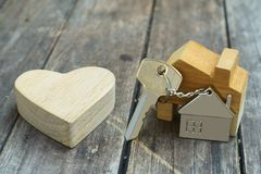 Home key with house keychain and wooden heart mock up on vintage wood background, home sweet home concept. Real estate royalty free stock photography