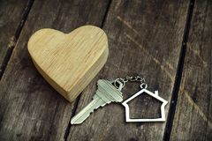 Home key with house keychain and wooden heart mock up on vintage wood background, home sweet home concept. Copy space royalty free stock photography