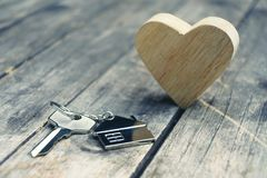 Home key with house keychain and wooden heart mock up on vintage wood background, home sweet home concept. Copy space stock images