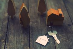 Home key with house keychain and wooden tree and home mockup on vintage wood background, property concept. Copy space royalty free stock photos