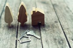 Home key with house keychain and wooden tree and home mockup on vintage wood background, property concept. Copy space royalty free stock photo