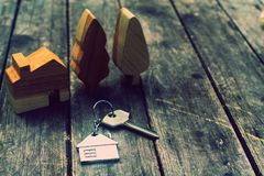 Home key with house keychain and wooden tree and home mockup on vintage wood background, property concept. Copy space, dark tone royalty free stock image