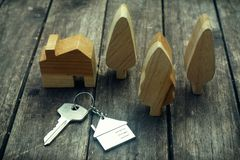 Home key with house keychain and wooden tree and home mockup on vintage wood background, property concept. Copy space stock images