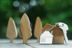 Home key with house keychain and wooden treen and home mock up on vintage wood background, property concept. Copy space royalty free stock images