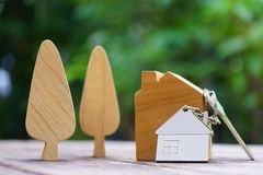 Home key with house keychain and wooden treen and home mock up on vintage wood background, property concept. Copy space royalty free stock photo