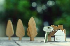 Home key with house keychain and wooden treen and home mock up on vintage wood background, property concept. Copy space royalty free stock photography