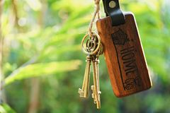 Home key with house keyring hanging with blur garden background. Free space royalty free stock photo