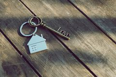 Home key with love house keyring on wood background. Free space Royalty Free Stock Photography