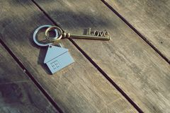 Home key with love house keyring on wood background. Free space Royalty Free Stock Photos