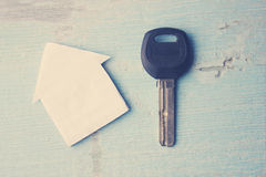 Home and key. Paper  home  and  key  on the  wooden  table Stock Photos
